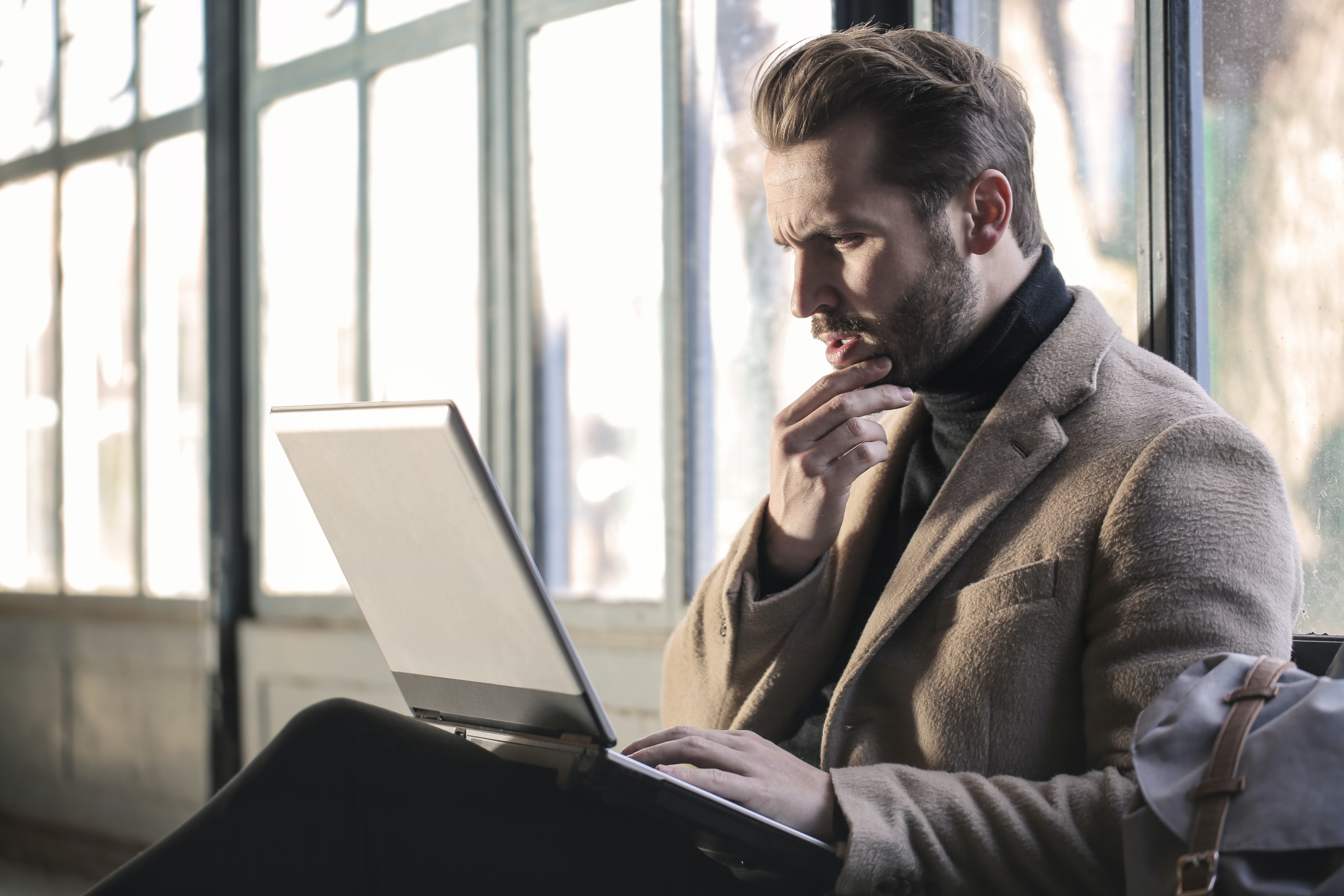 Man in thought while looking at laptop screen